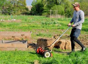 Joel Ruffner mowing at the community gardens